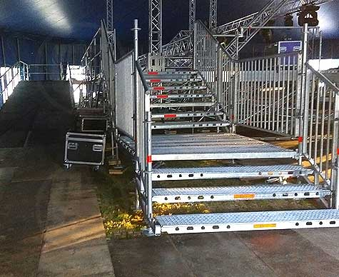 Layher substage structure with loading ramp and access steps.