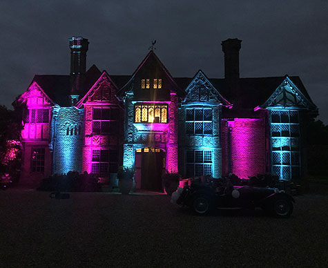 Mansion exterior lit at night in magenta and cyan light.