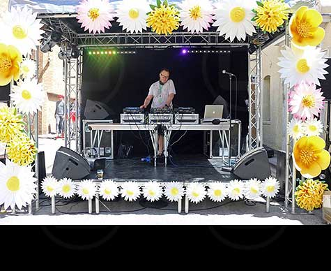 Small covered DJ stage for street event.