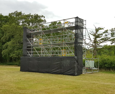 Typical Layher support structure for drive-in cinema screen on grass.